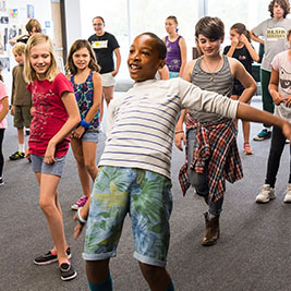 A group of students look at one student dancing at the front.