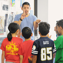 A teacher holds up a finger as students look on.