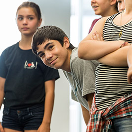 A student leans forward to peek at the camera as other students stand at attention.