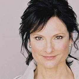 Susan Angelo is half Sicilian, half North Carolinian. She has short dark brown hair and wears a white shirt against a faded purple backdrop.