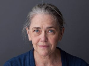 Deborah Strang is a vibrant older woman with grey hair and blue eyes. Her hair is tied back and she wears a blue shirt as she sits in front of a gray backdrop.