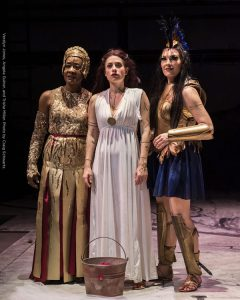 Hera, Medea, and Athena stand side by side as they look into the distance in this scene from Argonautika. Hera is wearing a gold dress, Medea is wearing a white dress, and Athena is wearing gold and dark blue warrior garb.
