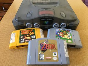 A dusty Nintendo 64 console with three used games: Donkey Kong, Super Mario, and The Legend of Zelda.