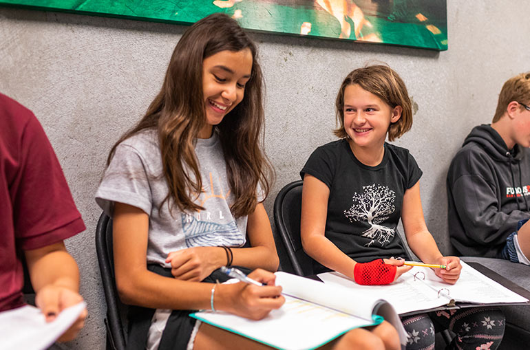 Two middle school students smile as they take notes on binders on their laps. The student on the left has long brown hair and a gray T-shirt. The student on the right has blond hair in a bob cut and a black T-shirt with a white tree on it.Two middle school students smile as they take notes on binders on their laps. The student on the left has long brown hair and a gray T-shirt. The student on the right has blond hair in a bob cut and a black T-shirt with a white tree on it.