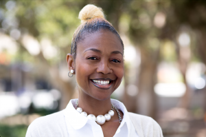 Nikysha Gilliam is a smiling African American woman with light colored hair styled in a bun. She wears pearl earrings and large pearl necklace and a white collared shirt as she stands against a blurred nature background.