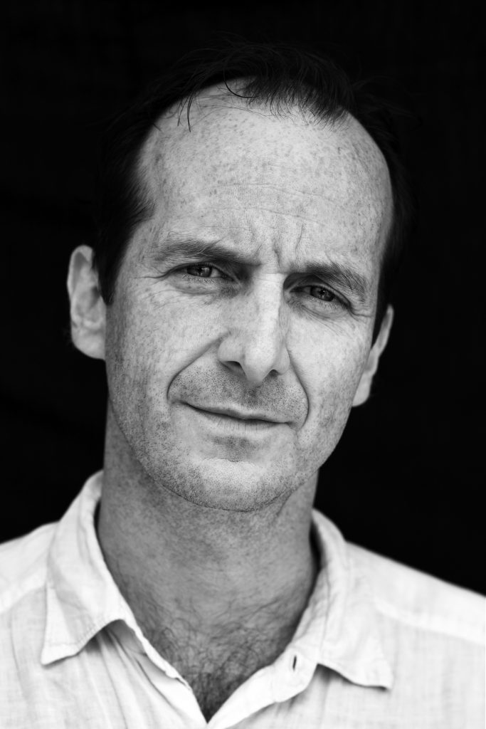 A black and white photo of Denis O'Hare. He is balding with dark hair and wears a collared shirt.