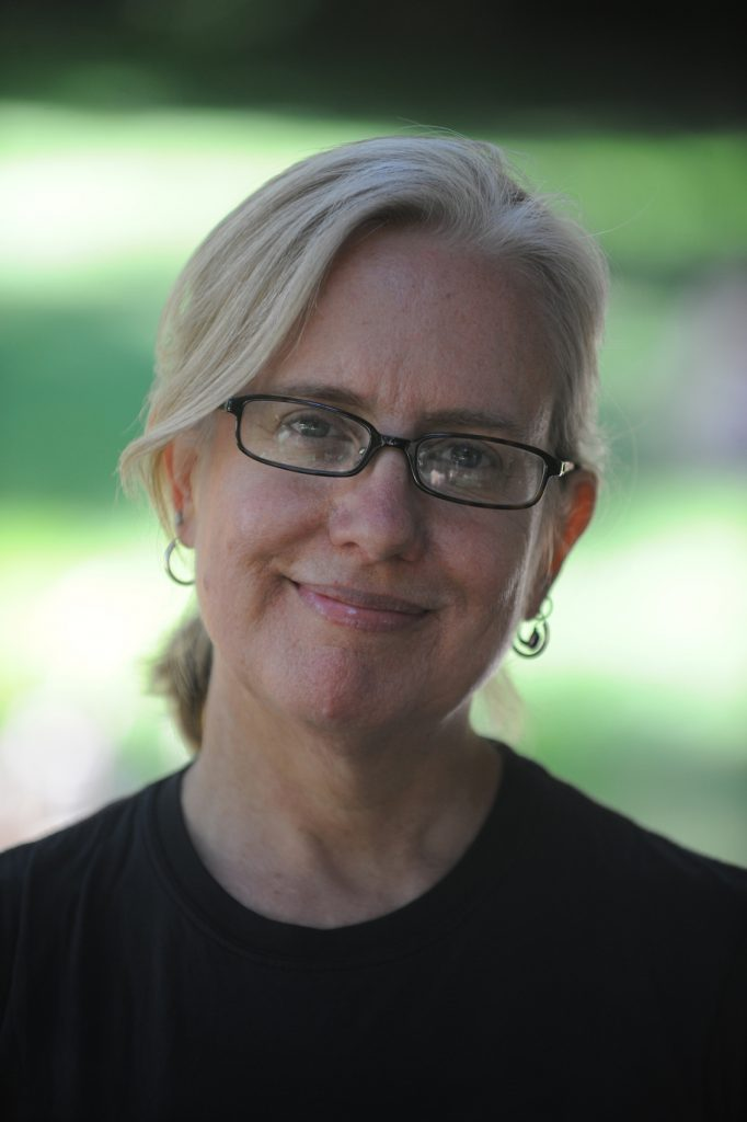 Lisa Peterson has blond hair tied back and black glasses and a black T shirt. She smiles in front of a blurred green background.