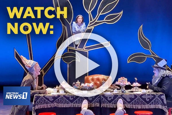 Watch Now. A play button overlays a scene from the Mad Tea Party in Alice in Wonderland. Alice gazes from a black tree outlined in gold as the March Hare in a knitted beanie and the Mad Hatter in a top hat laugh over a table of cakes and tea.