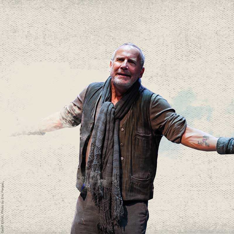 An older man with short gray hair and beard stubble opens his arms as if in challenge. He wears a bedraggled black vest over a gray shirt with the sleeves rolled up and gray fingerless gloves.