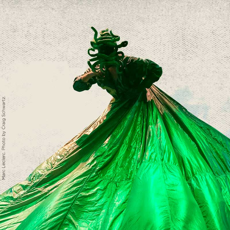 A tall green creature made of a mask with snakes curling over and around its face and a shimmering fabric wrapping around the waist holds up an arm and leans forward.