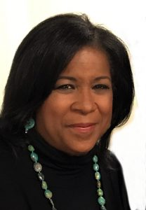 Susan Toler Car has shoulder length black hair and wears a turquoise necklace on a black sweater.